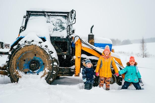 Crianças felizes na frente de um trator em um dia de inverno ao ar livre