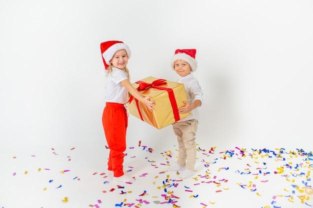 Crianças felizes no chapéu de papai noel segurando a caixa de presente grande. isolado no fundo branco venda, férias, natal, ano novo, conceito de natal.