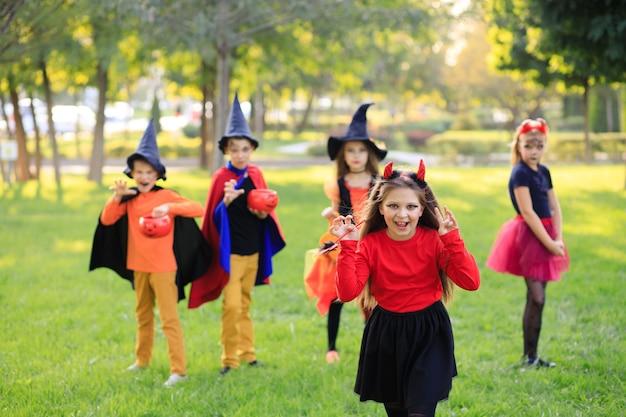 Crianças felizes no parque em fantasias de halloween comemoram o feriado