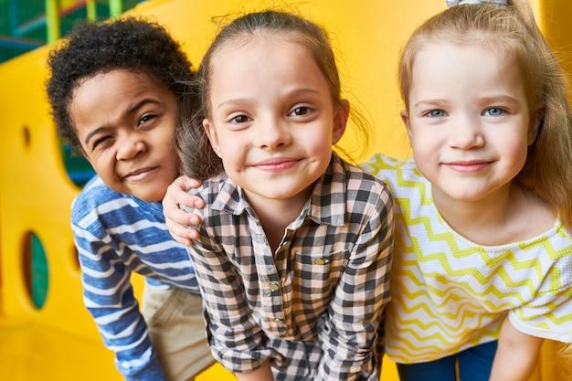 Crianças felizes, olhando para a frente no play center