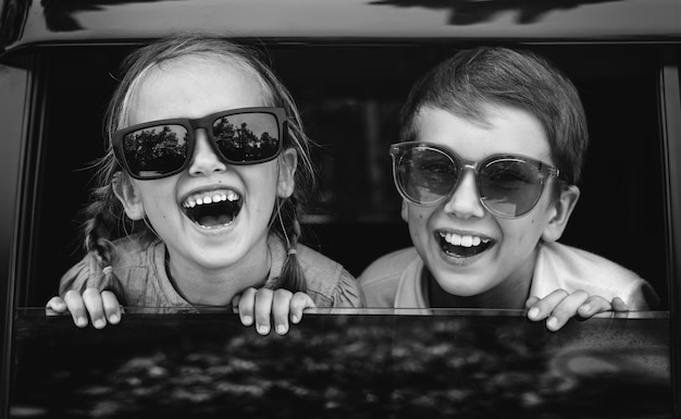 Crianças felizes, olhando pela janela do carro