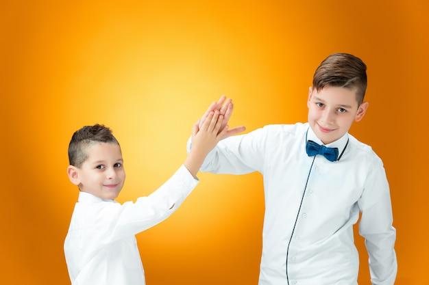 Crianças felizes, parabenizando pelas palmas das mãos com vitória