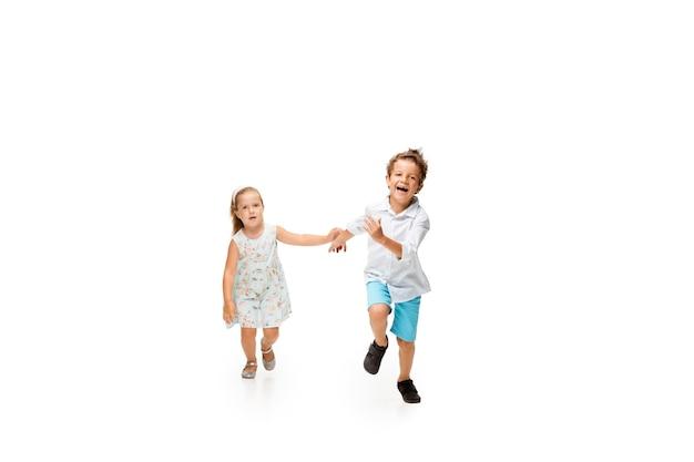 Crianças felizes, pequeno e emocional menino caucasiano e uma menina pulando e correndo, isolado no fundo branco. pareça feliz, alegre, sincero. copyspace para anúncio. infância, educação, conceito de felicidade.