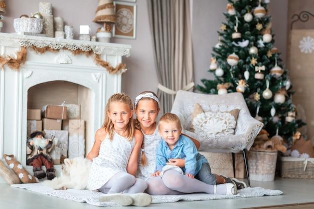 Crianças felizes perto da árvore de natal com presentes perto da lareira