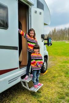 Crianças felizes perto de campista rv se divertindo, viagem de férias em família no motorhome