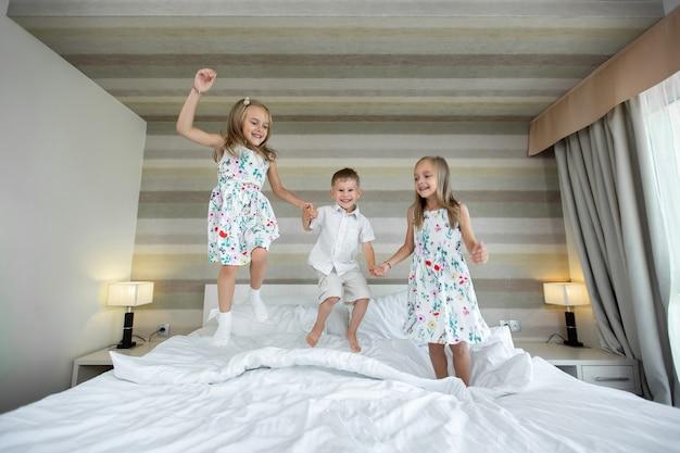 Crianças felizes pulando, se divertindo, brincando na cama no quarto
