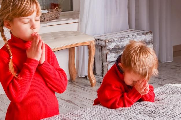 Crianças felizes rezando em casa para o natal