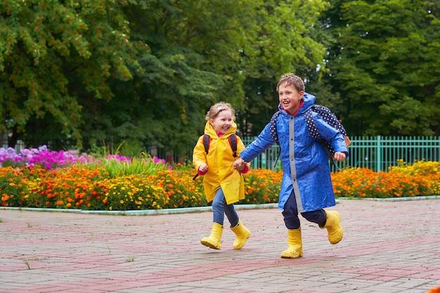 Crianças felizes riem correndo e correm para a escola vestidas com capas de chuva com uma maleta atrás de uma mochila.