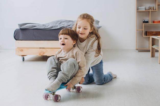 Crianças felizes, se divertindo com skates no chão no quarto em casa.