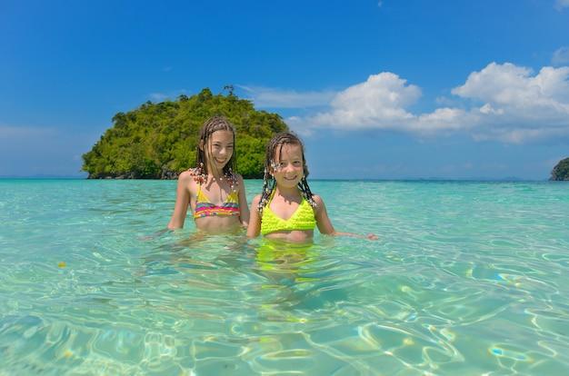 Crianças felizes, se divertindo no mar perto de islan tropical