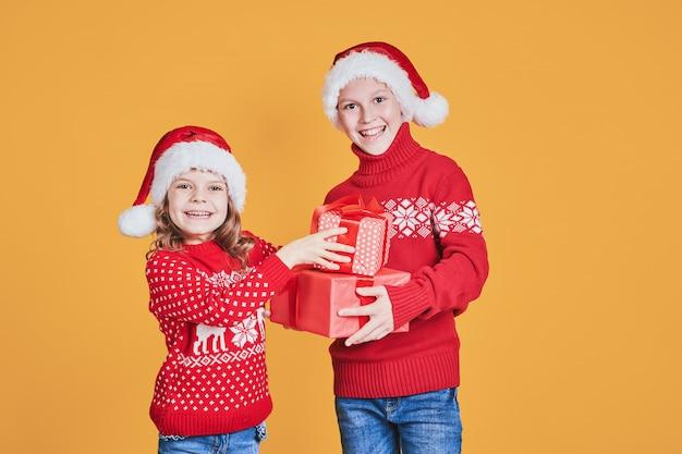 Crianças felizes, segurando caixas de presente vermelho