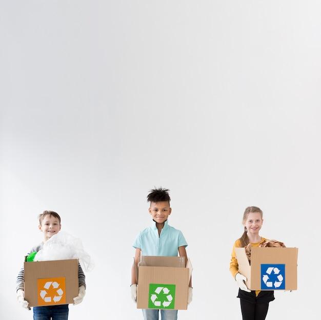Crianças felizes, segurando caixas de reciclagem