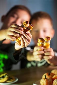 Crianças felizes segurando lanches de halloween em forma de múmia, feitos de massa e salsicha