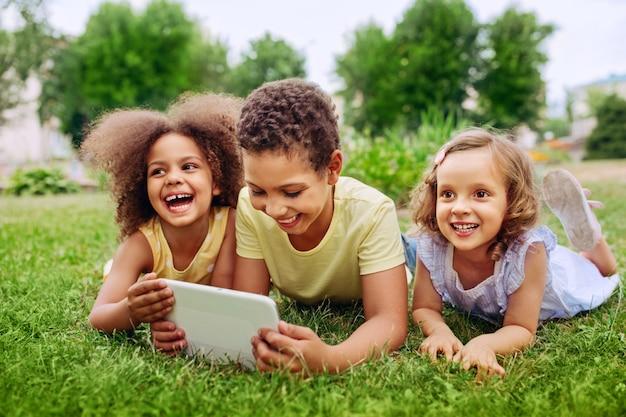 Crianças felizes segurando o tablet pc ao ar livre em um parque de verão em uma grama verde em um dia ensolarado