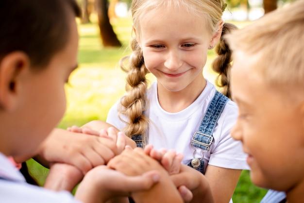 Crianças felizes, segurando pelas mãos no parque