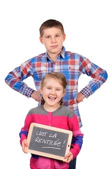 Crianças felizes segurando uma lousa