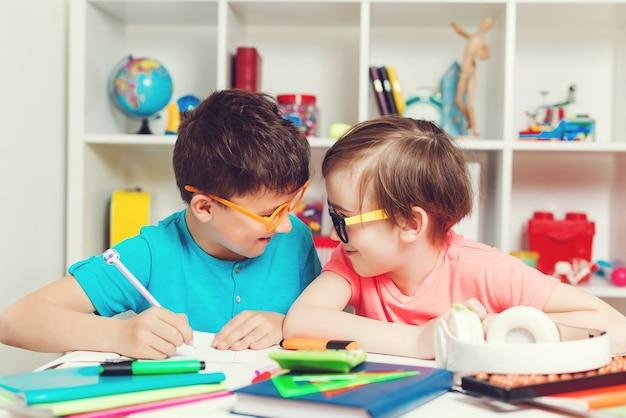 Crianças felizes sentadas na mesa e fazendo lição de casa.