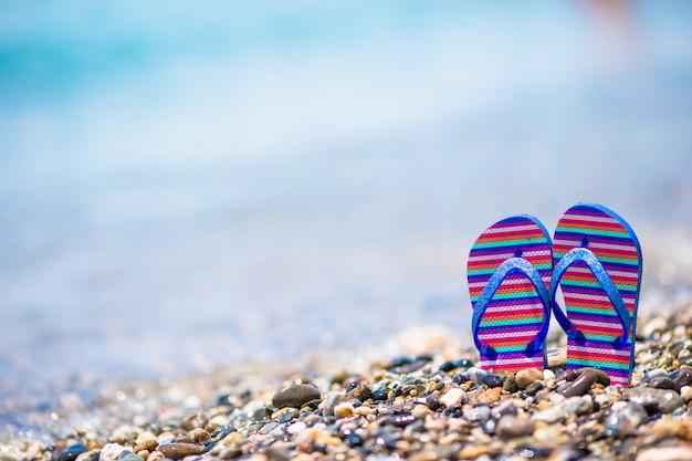 Crianças flip-flop na praia em frente ao mar