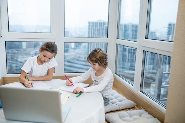 Crianças focadas escrevendo e pintando à mesa