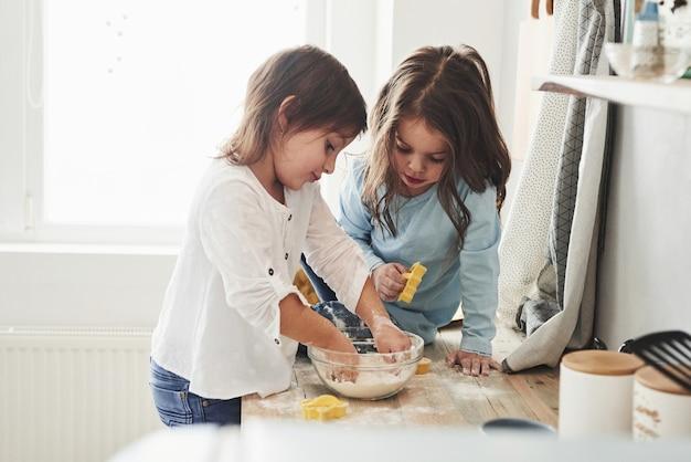 Crianças fofas. amigos da pré-escola aprendendo a cozinhar com farinha na cozinha branca.