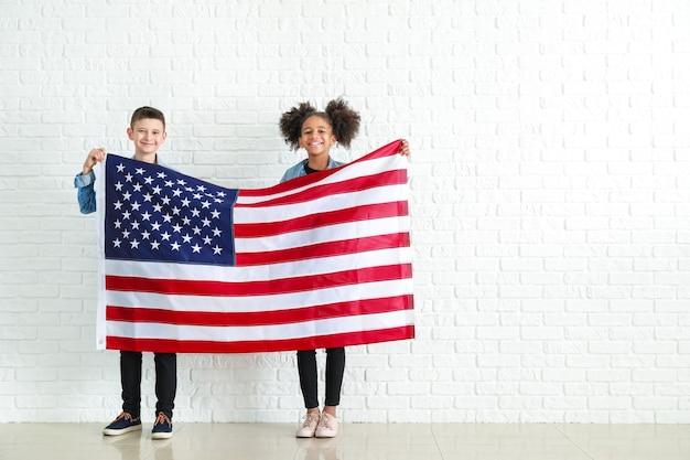 Crianças fofas com a bandeira nacional dos eua perto de uma parede de tijolos brancos