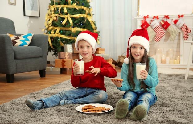 Crianças fofas com chapéu de papai noel bebendo leite e comendo biscoitos deliciosos em casa