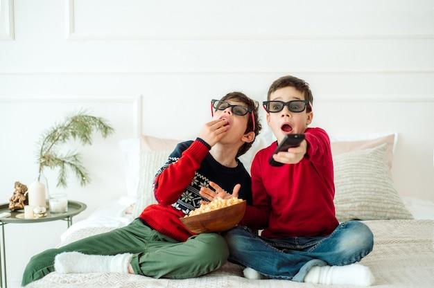 Crianças fofas comendo pipoca enquanto assistiam tv em casa em copos de 3 d.
