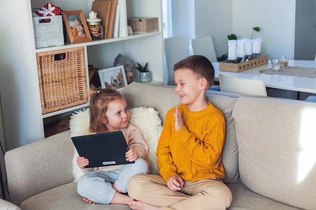 Crianças fofas falam por videochamada usando um tablet. quarentena. uma família. casa. acolhedor.