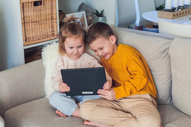 Crianças fofas falam por videochamada usando um tablet. quarentena. uma família.