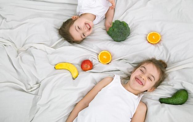 Crianças fofas felizes brincam com frutas e vegetais sobre um fundo claro. alimentação saudável para crianças.