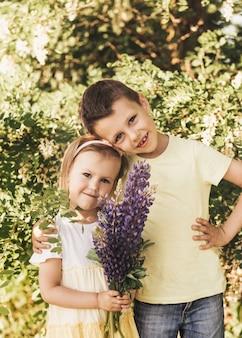 Crianças fofas felizes, irmão e irmã, menino e menina na natureza no abraço do parque, amizade verdadeira