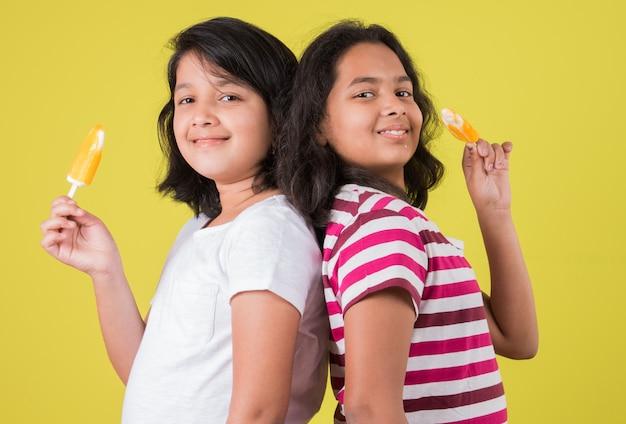 Crianças fofas indianas ou asiáticas comendo sorvete ou barra de manga ou doce. isolado sobre fundo colorido