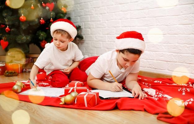 Crianças fofas meninos escrevem a carta para o papai noel perto da árvore de natal