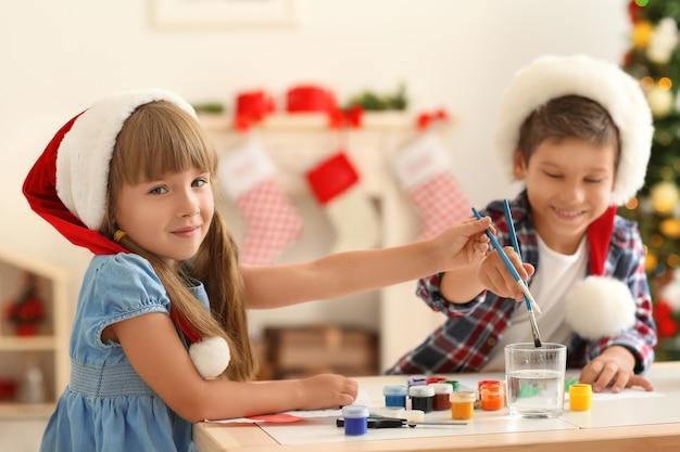 Crianças fofas pintando quadros para o natal na mesa