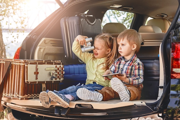 Crianças fofas se divertindo no porta-malas de um carro com malas de viagem familiar