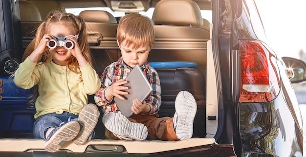 Crianças fofas se divertindo no porta-malas de um carro preto com malas de família