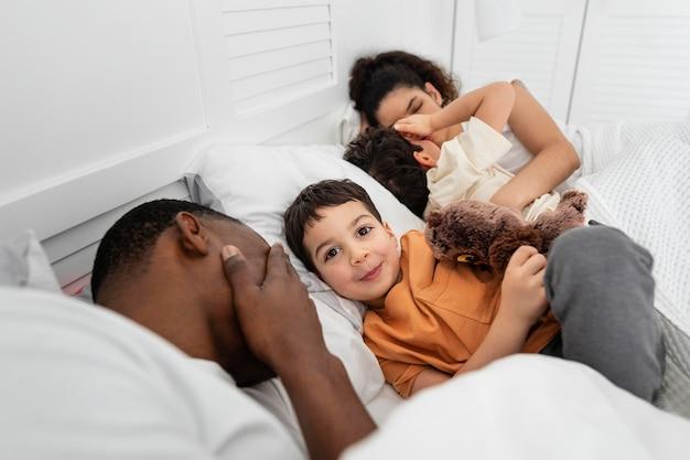 Crianças fofas tentando dormir ao lado dos pais