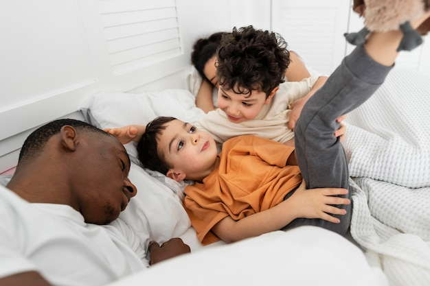 Crianças fofas tentando dormir com os pais