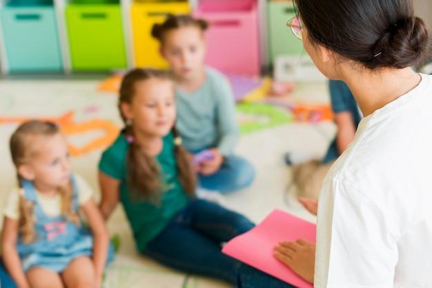 Crianças fora de foco prestando atenção ao professor