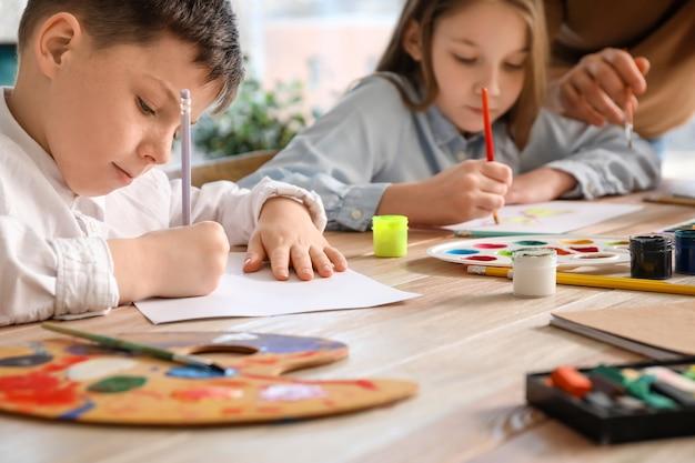 Crianças frequentando aulas opcionais de desenho na escola