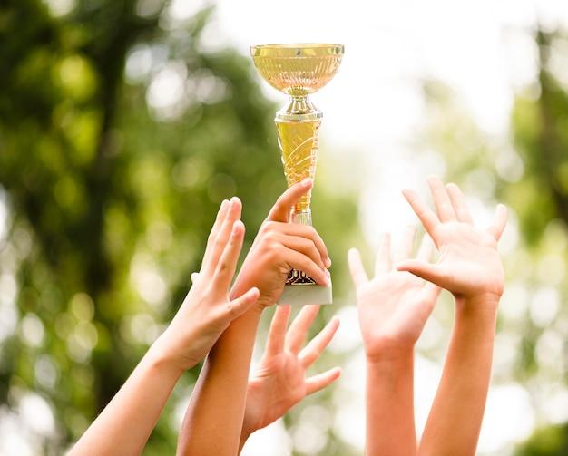 Crianças ganhando um troféu depois de vencer uma partida de futebol de perto