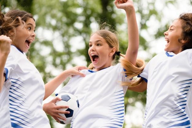 Crianças ganhando uma partida de futebol lá fora