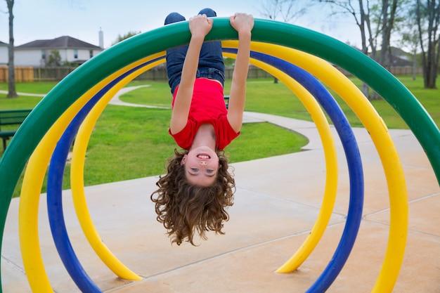 Crianças garoto garota de cabeça para baixo em um anel de parque