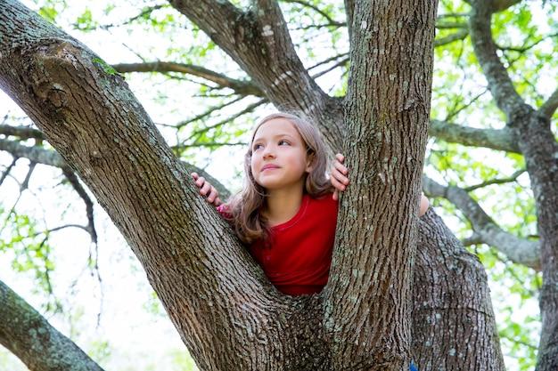 Crianças garoto garota jogando escalada para uma árvore em um parque