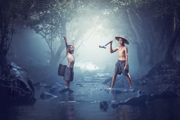 Crianças gostavam de pescar em riachos, dois meninos felizes e sorrir, tailândia