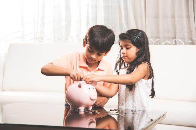 Crianças indianas asiáticas fofas guardando moedas no cofrinho em casa