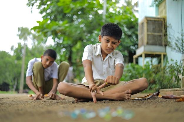 Crianças indianas brincando com bolinhas de gude