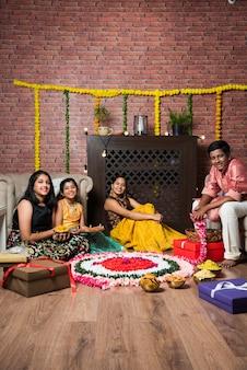 Crianças indianas celebrando diwali, deepawali, bhai dooj ou rakhi ou raksha bandhan com flores rangoli, presentes, diya