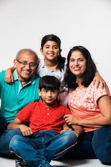 Crianças indianas com avós sorrindo enquanto estão sentadas em um fundo branco dentro de casa, foco seletivo