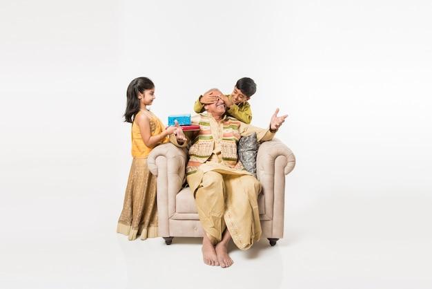 Crianças indianas com o avô sentado em um sofá, vestindo roupas tradicionais em algum dia de festival, compartilhando presentes e doces